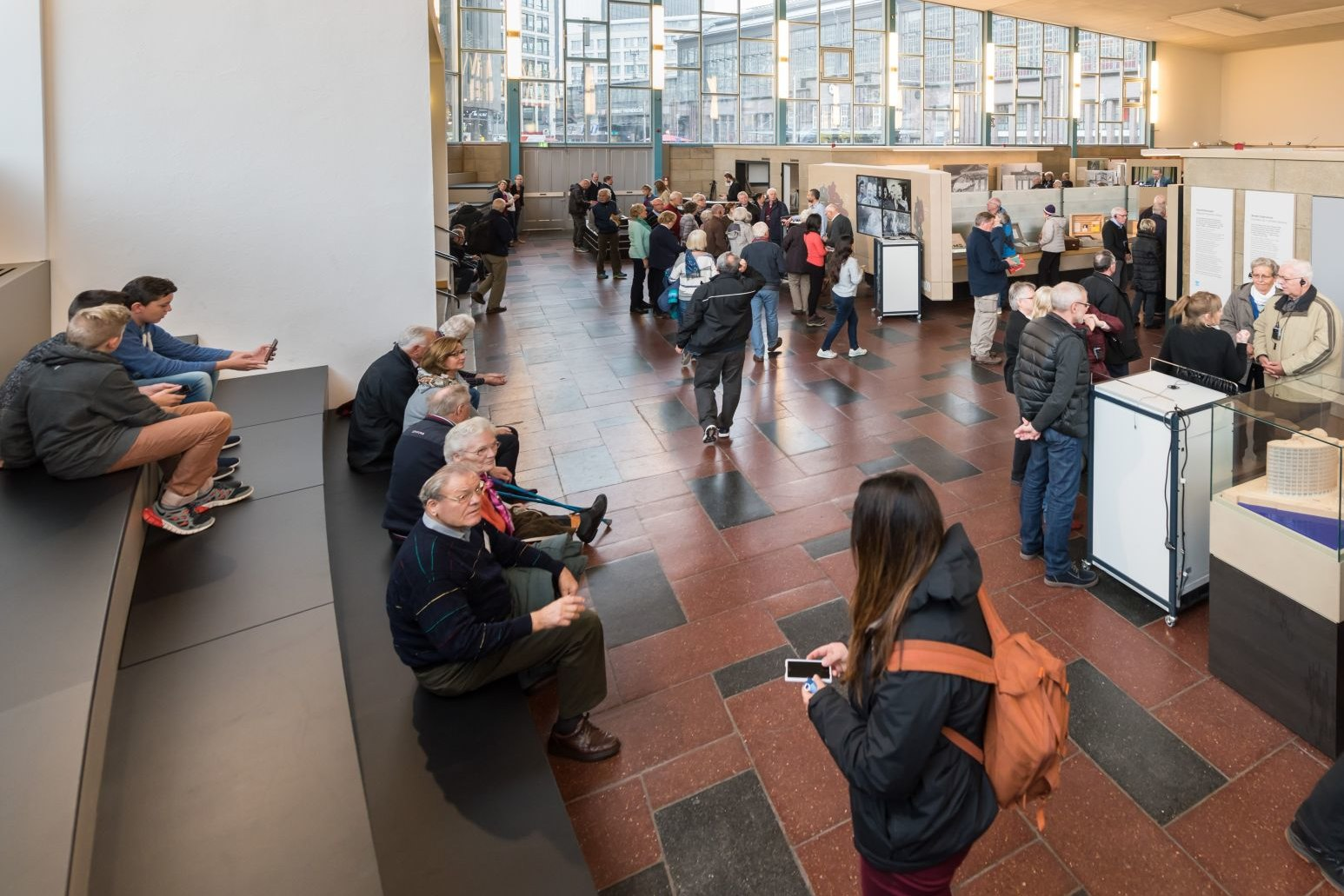 Großer Raumeindruck des Tränenpalastes mit vielen Besuchern, durch die große Glasfront ist der Bahnhof Friedrichstraße zu sehen