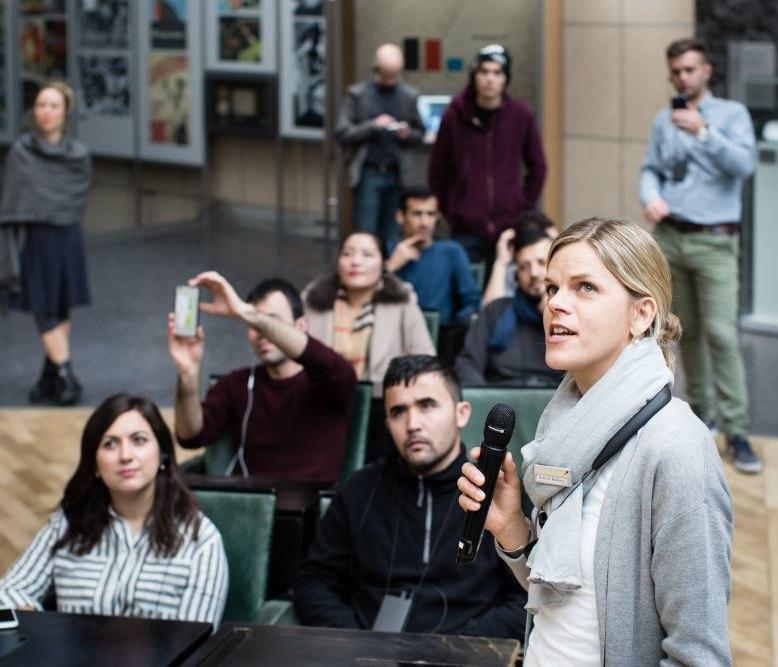Eine Gruppenbegleiterin spricht zu Besuchern im Bundestagsgestühl