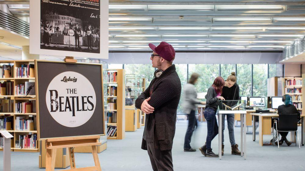 Auf einer Staffelei steht ein steht ein Bilderrahmen mit einem Trommelfell der Basstrommel der Beatles, darüber hängt ein Plakat der Bravo Beatles Blitztournee 1966. Neben der Staffelei steht ein junger Mann mit Mütze und betrachtet sie.