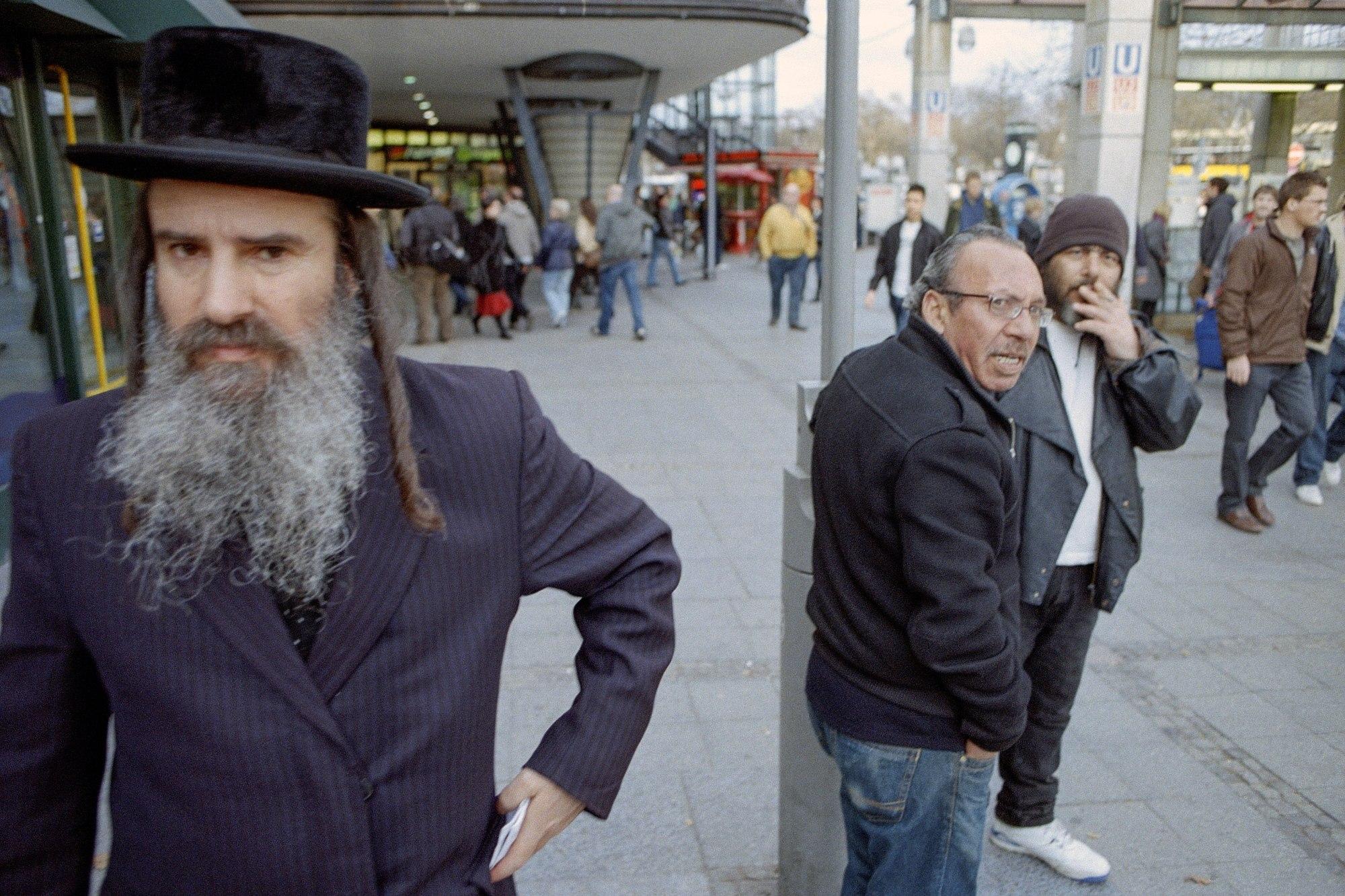 Ein älterer Mann mit Hut, Bart und Schläfenlocken steht auf einem belebten Platz und blickt in die Kamera.