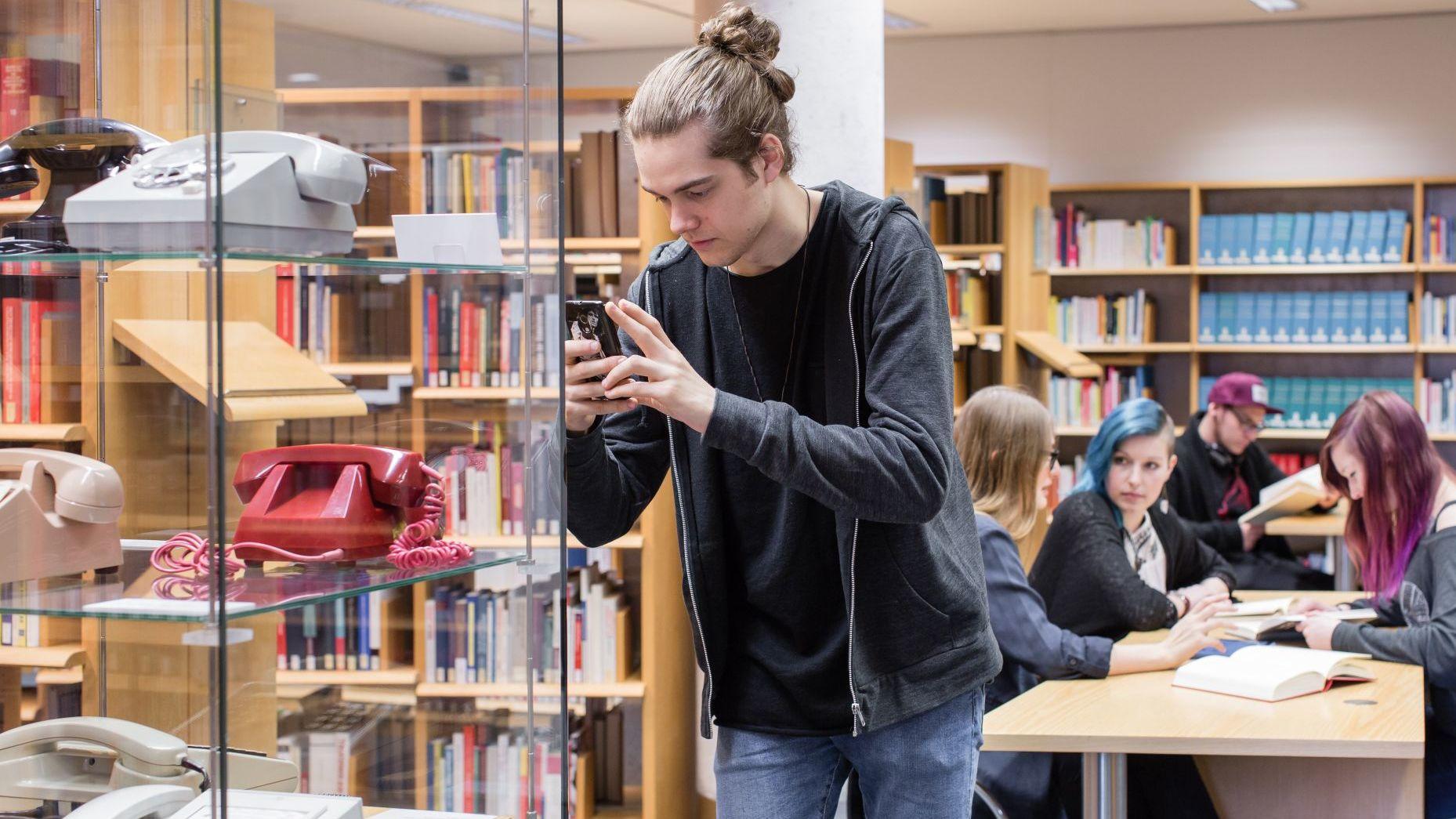 """Ein Besucher macht ein Handyfoto von Objekten der Ausstellung """"Objektgeschichten"""" im Informationszentrum."""