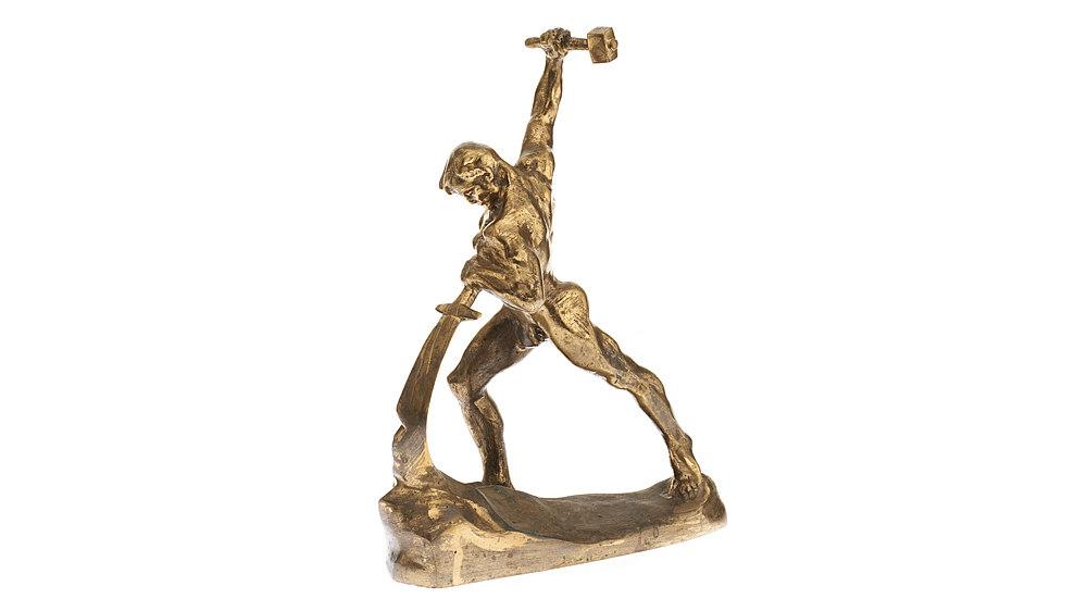Muskulöser Mann in Schrittstellung, der mit der linken Hand ein Schwert verbiegt. In der rechten nach oben gehobenen Hand hält er einen Hammer.