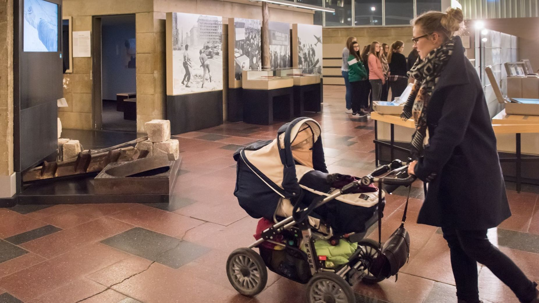 Eine junge Frau schiebt einen Kinderwagen über die Steinfliesen des Tränenpalastes, im Hintergrund die Ausstellung