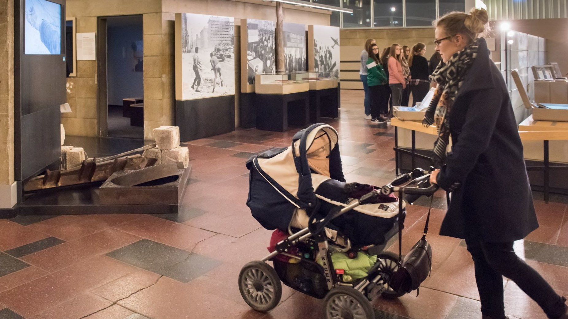 A young woman is walking through the exhibition with a buggy