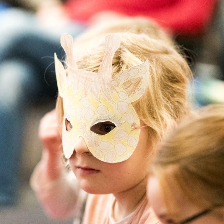 Ein kleines Mädchen trägt eine Maske im Haus der Geschichte