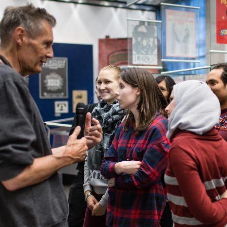 Ein Gruppenbegleiter führt Jugendliche durch die Dauerausstellung in Bonn