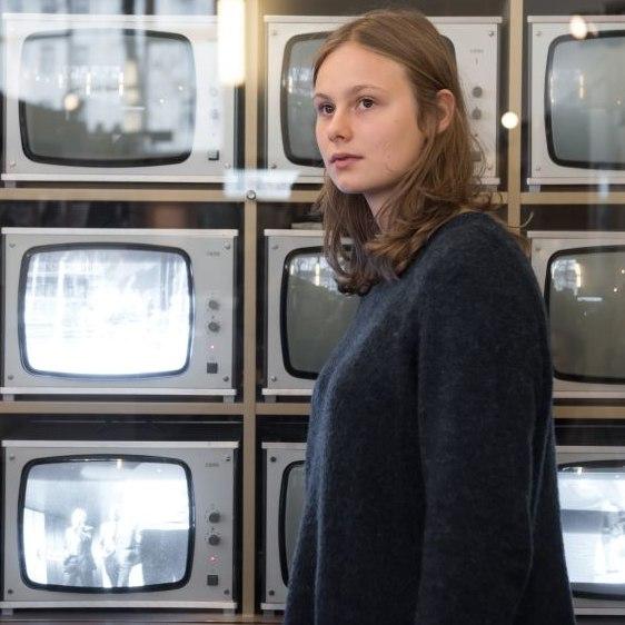 Eine Besucherin steht vor einer Wand mit Überwachungsmonitoren im Tränenpalast