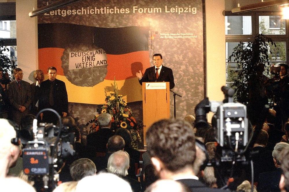 Gerhard Schröder am Rednerpult, dahinter ein großes Plakat mit der Aufschrift Zeitgeschichtliches Forum Leipzig, vor ihm Besucher und Pressevertreter