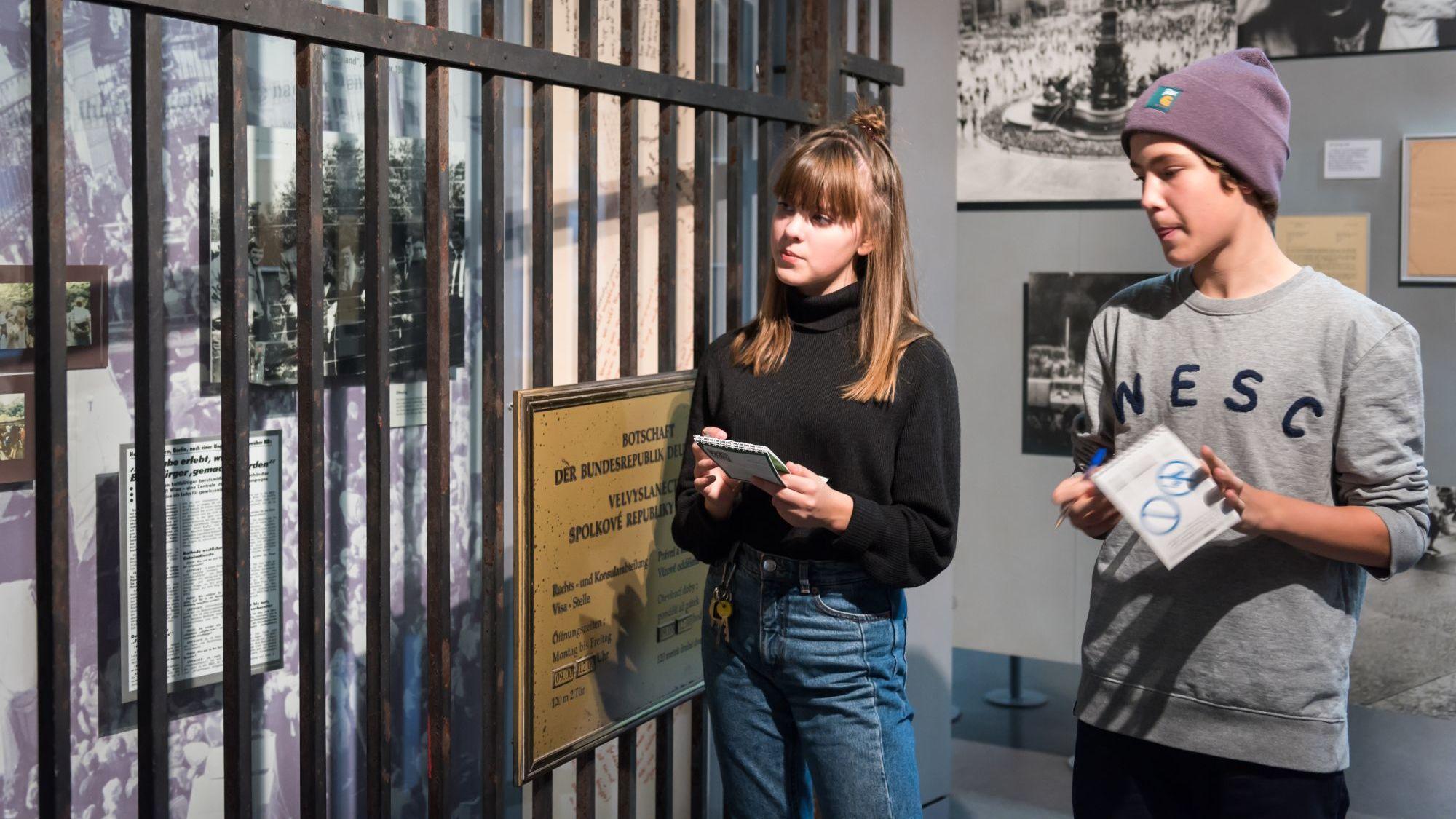 Zwei Jugendliche stehen in der Ausstellung neben einem Tor an dem ein Schild hängt Botschaft der Bundesrepublik Deutschland