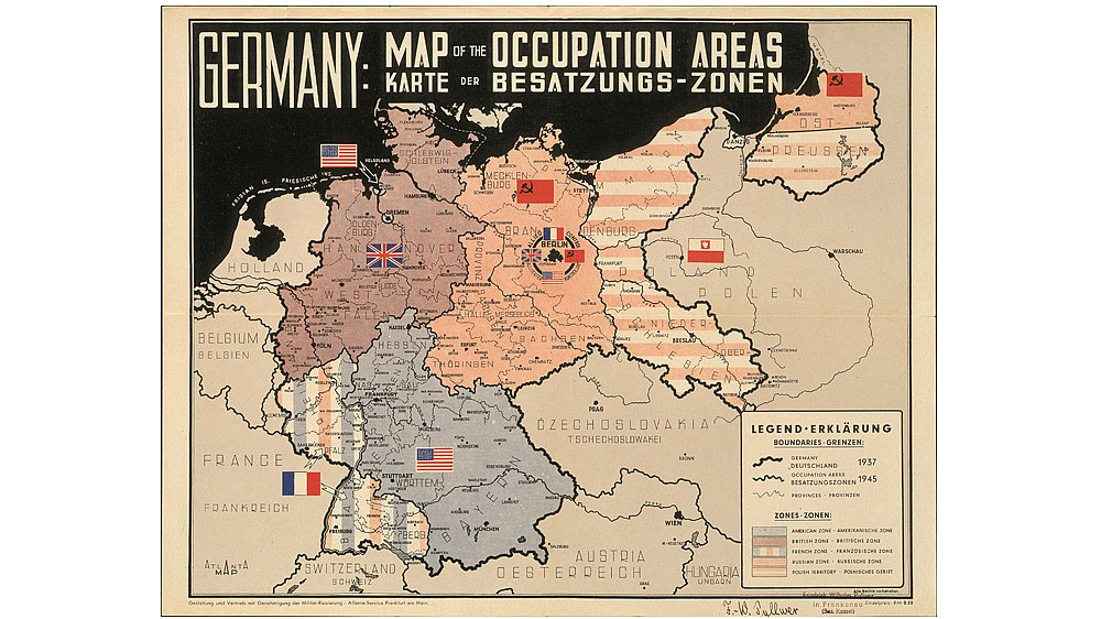 Zweisprachige Karte mit farblich abgesetzter Zoneneinteilung, darin jeweils eine Nationalflagge der Besatzer.