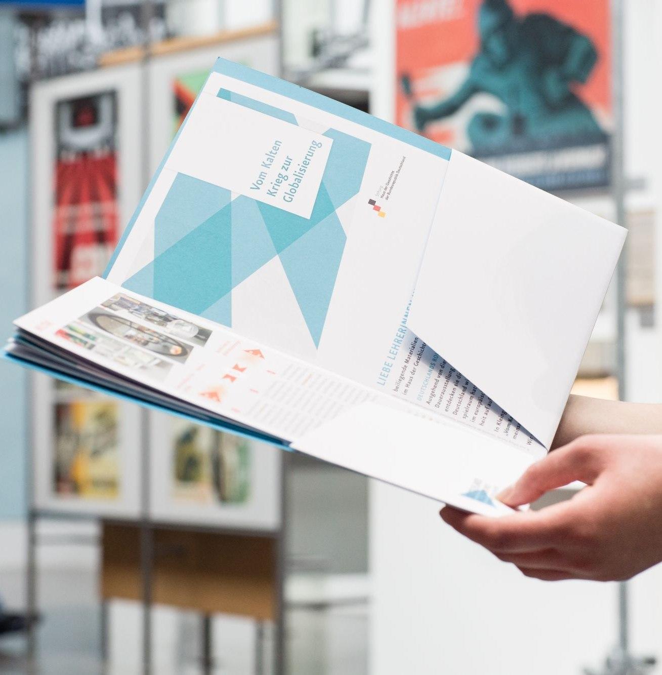 Eine Besucherin betrachtet eine Materialmappe in der Dauerausstellung