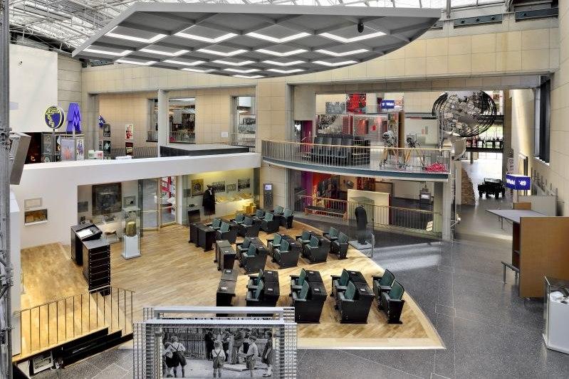 Blick aus der Vogelperspektive in einen großen Ausstellungsraum, in dessen Zentrum die Klappbänke aus dem Bundestag stehen.