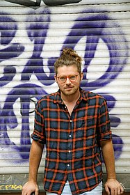 Porträtfoto des bildenden Künstlers Philipp Baumgarten vor Graffito