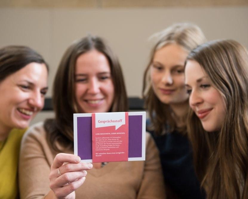 Besucherinnen betrachten das Kartenset 'Gesprächsstoff'