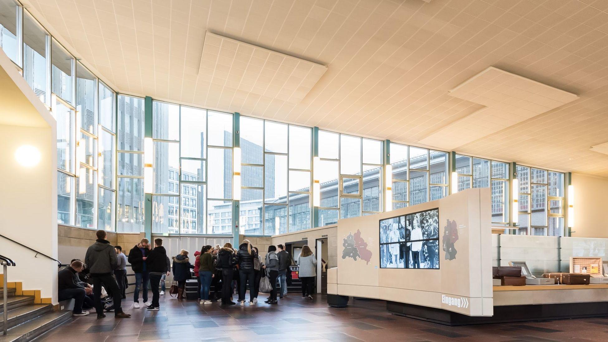 Blick in die große ehemalige Ausreisehalle und den Eingangsbereich der Ausstellung. Besucher stehen vor der großen Fensterfront, hinter der man u.a. den Bahnhof Friedrichstraße sieht