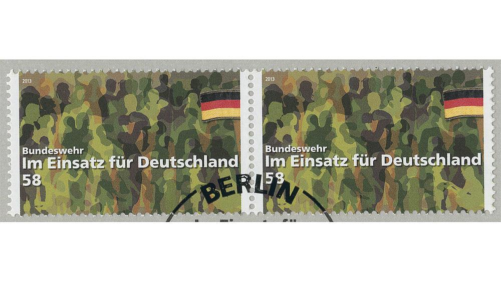 Auf der Schmuckkarte mit Sonderpostwertzeichen sind Silhouetten von Bundeswehrangehörigen in Camouflagefarben abgebildet. Darunter steht: 'Im Einsatz für Deutschland'.