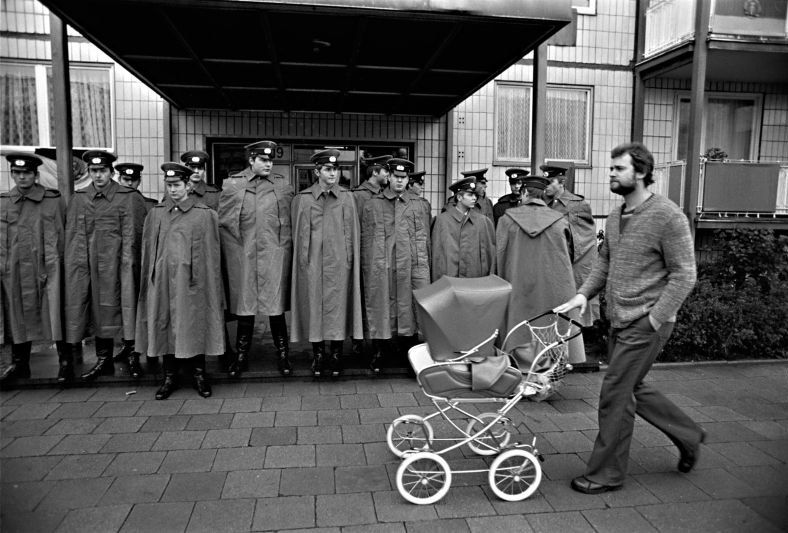 Photography: Man with pushchair in front of police officers on Karl-Marx-Allee in East Berlin, 1978