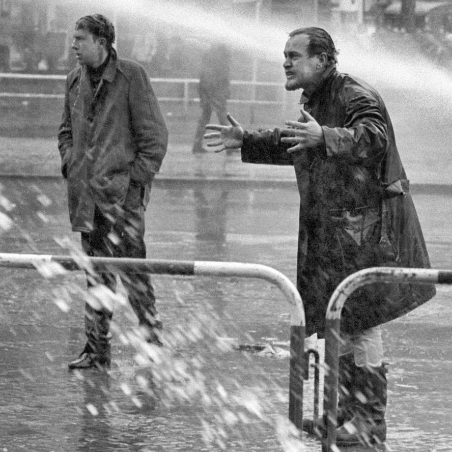 Mann im Strahl eines Wasserwerfers auf einer Straße.