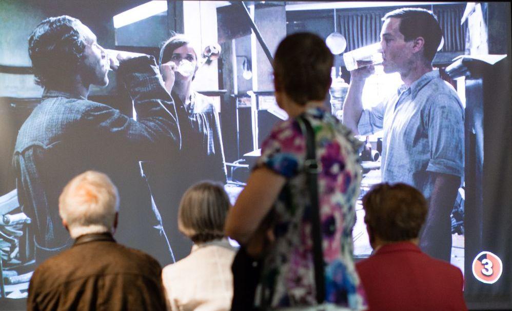 Drei Personen schauen sitzend, eine stehend auf eine große Filmprojektion mit drei jungen Männern, die gerade aus ihren Biergläsern trinken