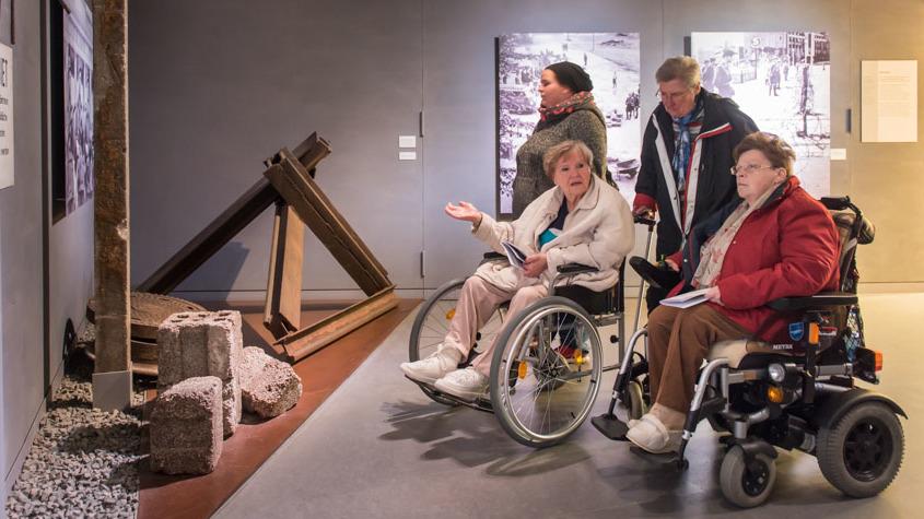 Zwei Rollstuhlfahrerinnen unterhalten sich in der Ausstellung