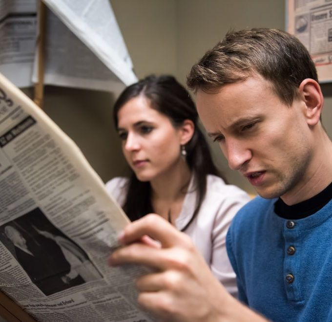 Besucher lesen eine Zeitung in der Dauerausstellung in Leipzig