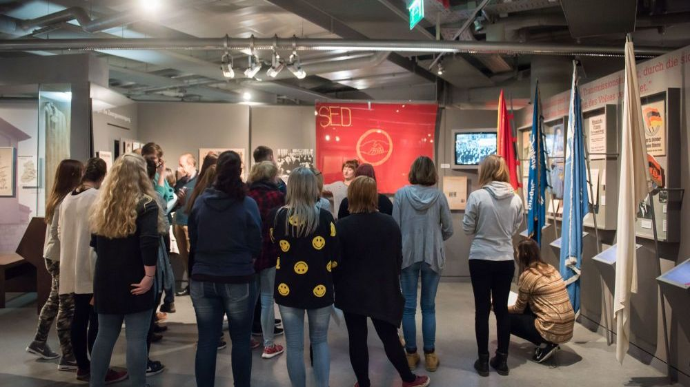 A group is standing in front of a SED-flag in an exhibition room