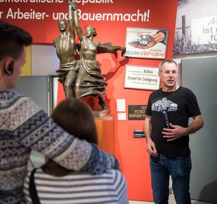 Ein Gruppenbegleiter spricht zu Besuchern in der Dauerausstellung in Berlin