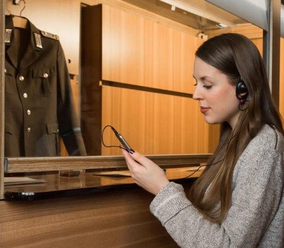 Besucherin mit Kopfhörern und Smartphone an der Grenzkabine im Tränenpalast