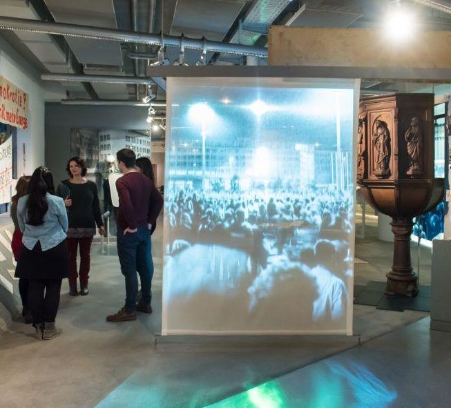 Besucher stehen vor Transparenten in der Dauerausstellung in Leipzig