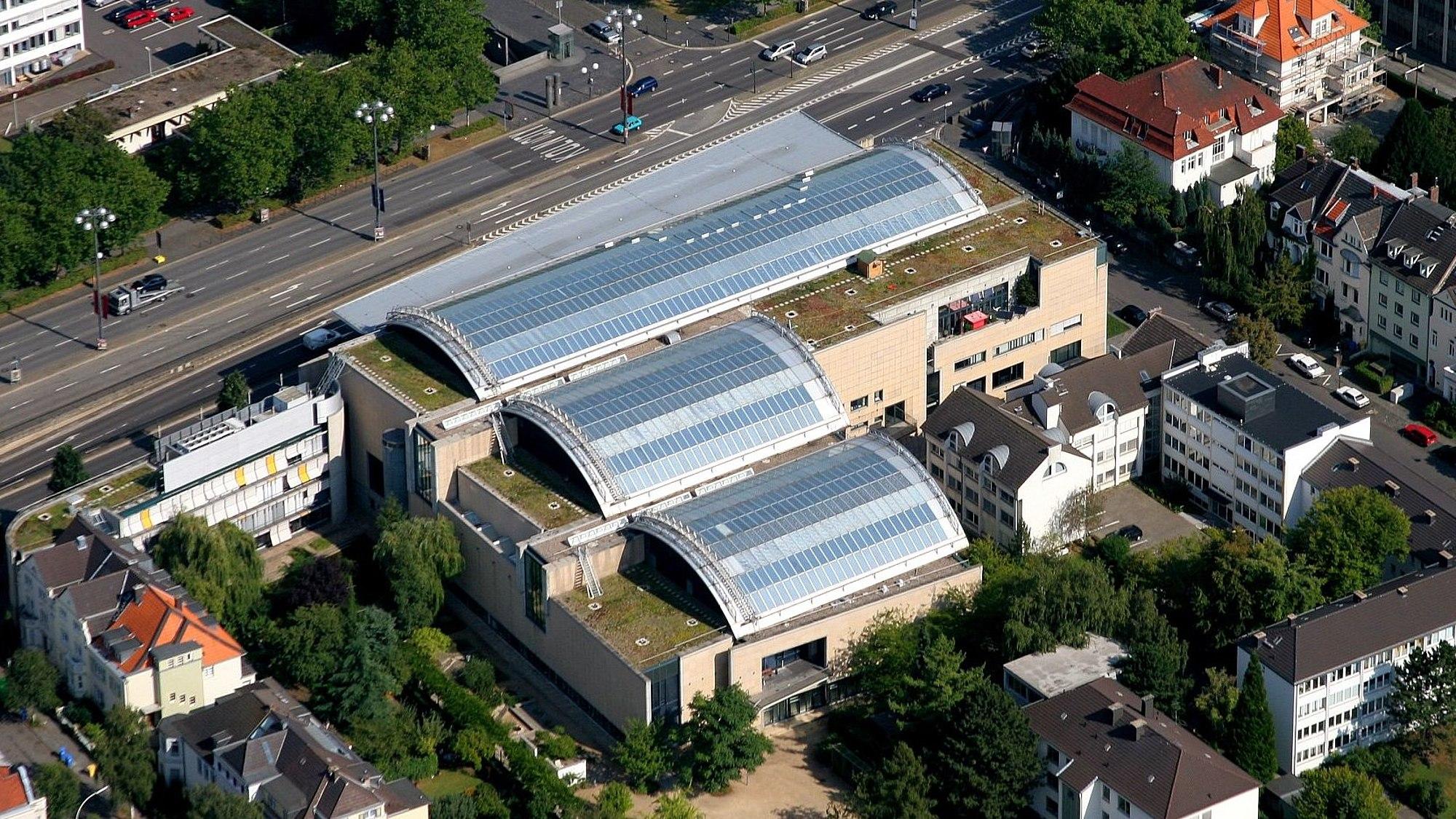 Vogelperspektive auf das Haus der Geschichte in Bonn, man sieht die drei Bögen des Glasdaches