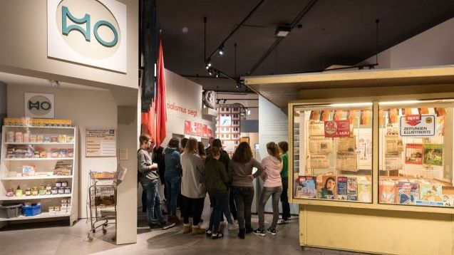 Eine Gruppe Jugendlicher steht zwischen einem alten Zeitungskiosk und einem Lebensmittelgeschäft