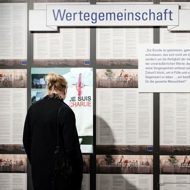 Besucherin vor einer Wand mit der Charta der Grundrechte der europäischen Union in allen Sprachen der EU