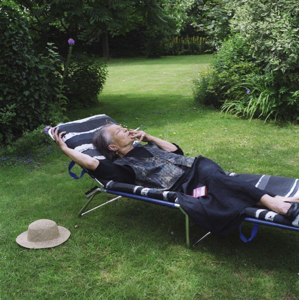 Eine Seniorin liegt ausgestreckt und rauchend auf einer Gartenliege, um sie herum Rasen und Büsche, neben ihr ein Strohhut auf dem Gras