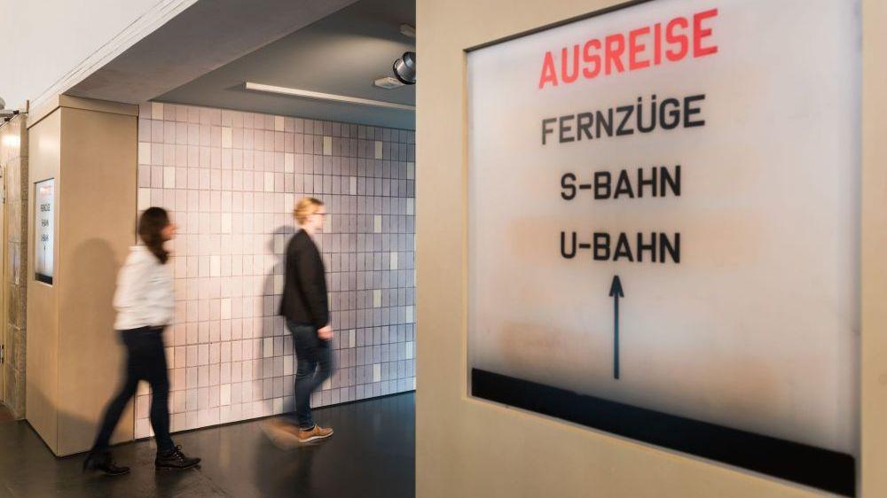 Besucherinnen gehen in Richtung Ausreise-Schild