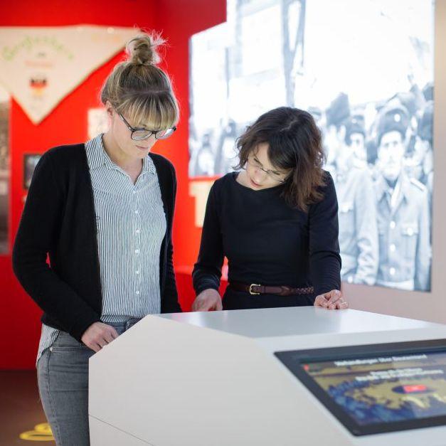 Zwei junge Frauen stehen in einem Ausstellungsraum über einen Monitor gebeugt