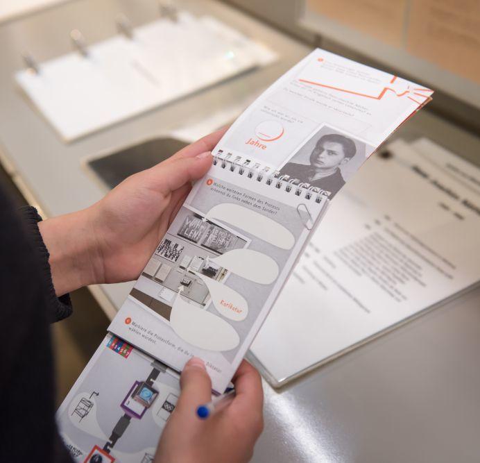 Besucher mit Spurensuche-Block in der Dauerausstellung in Leipzig