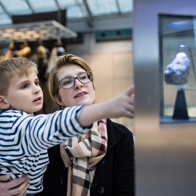 Ein kleiner Junge auf dem Arm seiner Mutter zeigt auf einer Vitrine, in der ein etwa faustgroßer Gesteinsbrocken präsentiert wird