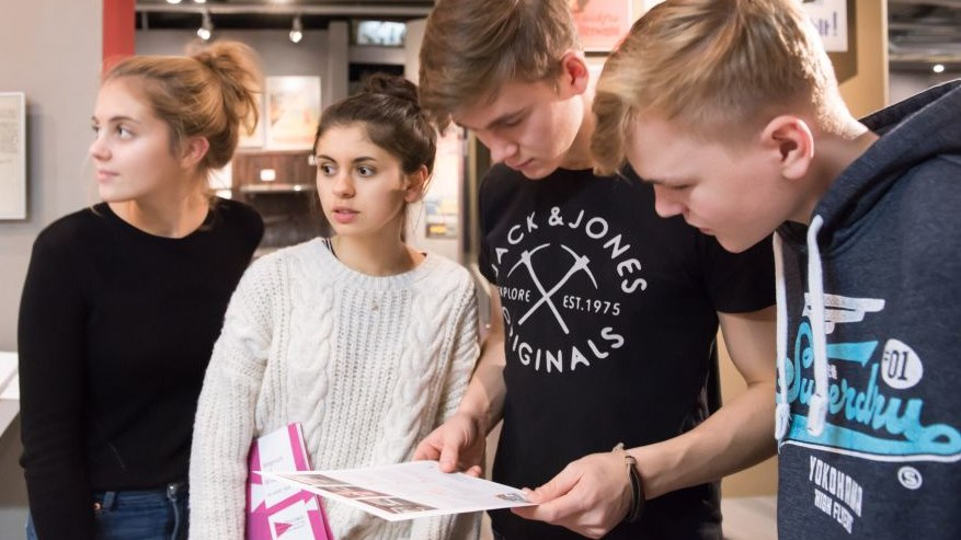 Vier Jugendliche stehen nebeneinander, die beiden Jungen sind über die Themenmappe gebeugt, die beiden Mädchen schauen in den Ausstellungsraum