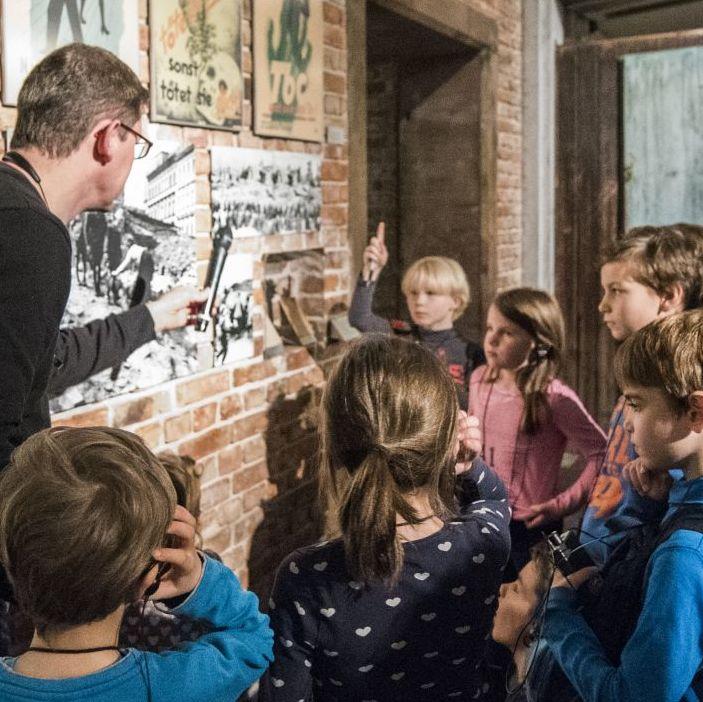 Kinder nehmen an einer Begleitung in der Dauerausstellung teil