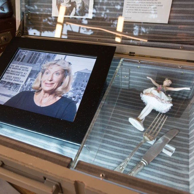An open suitcase, the tablet on the left is showing a video of the contemporary witness Sigline, on the right a small porcelain figure.
