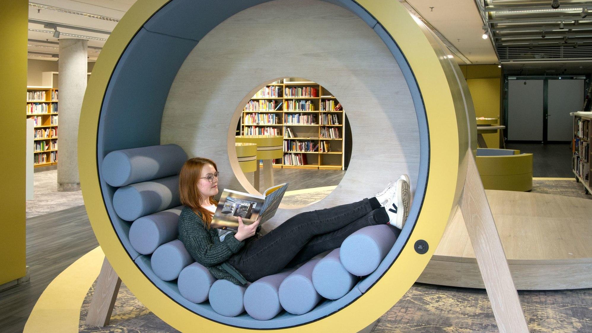 Eine Besucherin sitzt in der Lounge und liest
