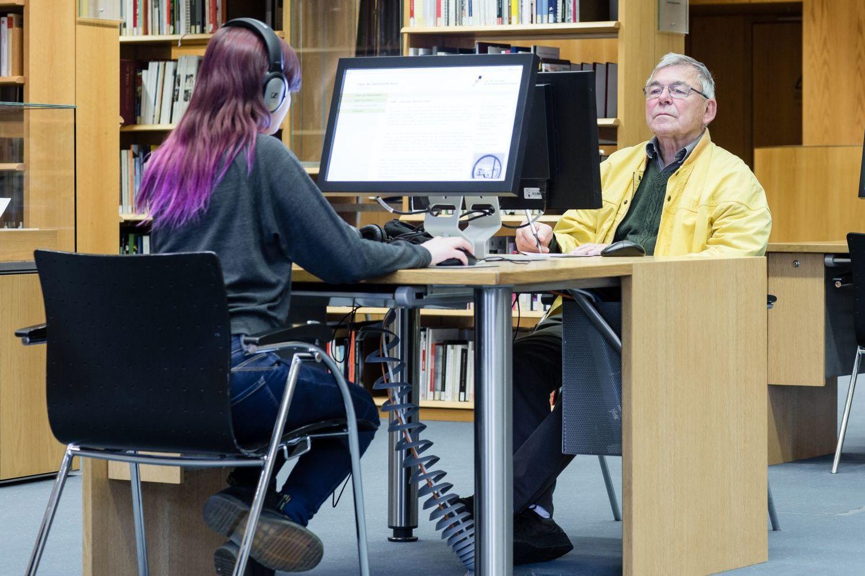 Besucher des Informationszentrum bei ihrer Recherche an den Computern.