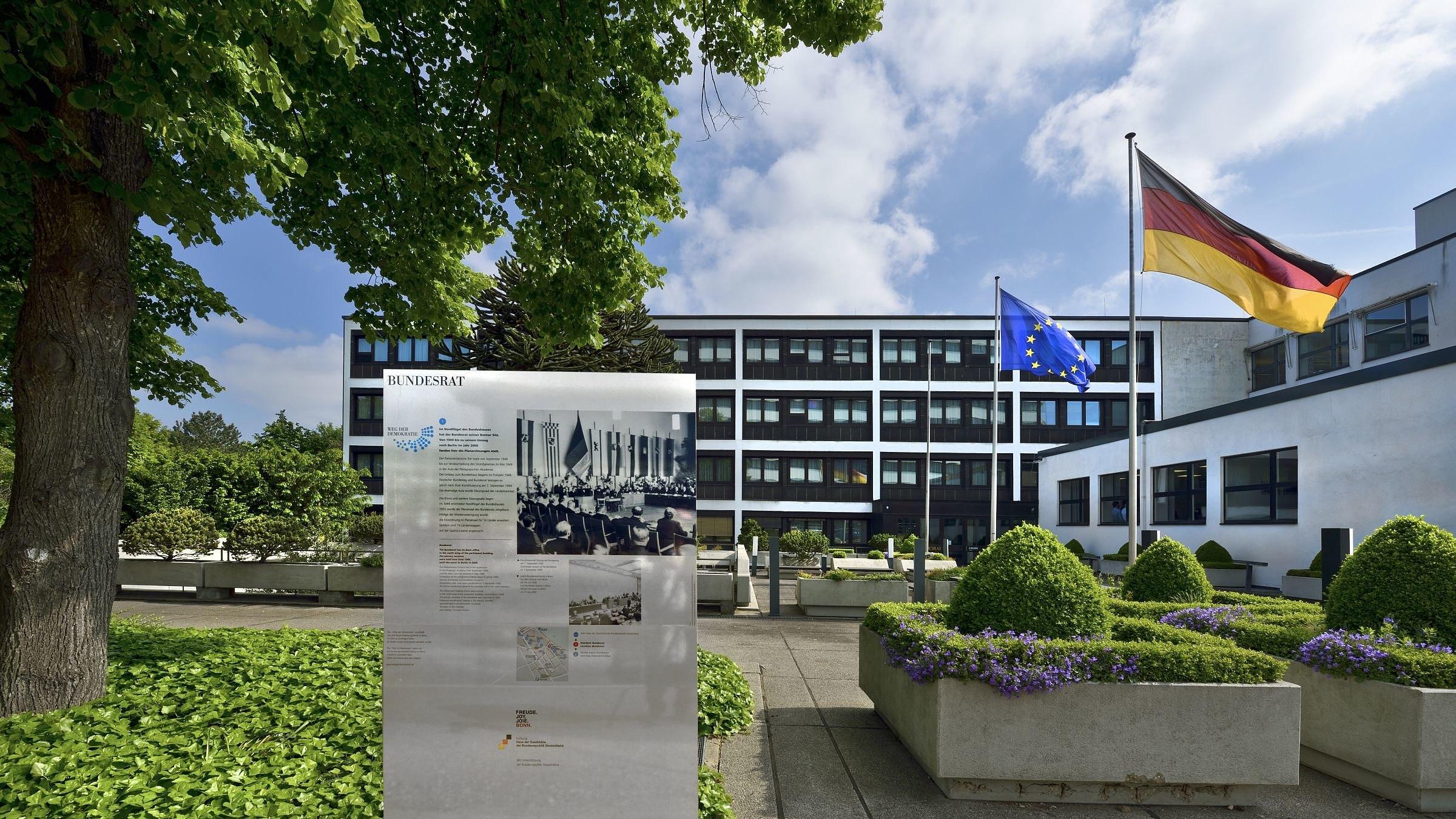 Blick auf den Nordflügel des Bundeshauses Bonn. Im Vordergrund die Tafel mit den Informationen zum Weg der Demokratie