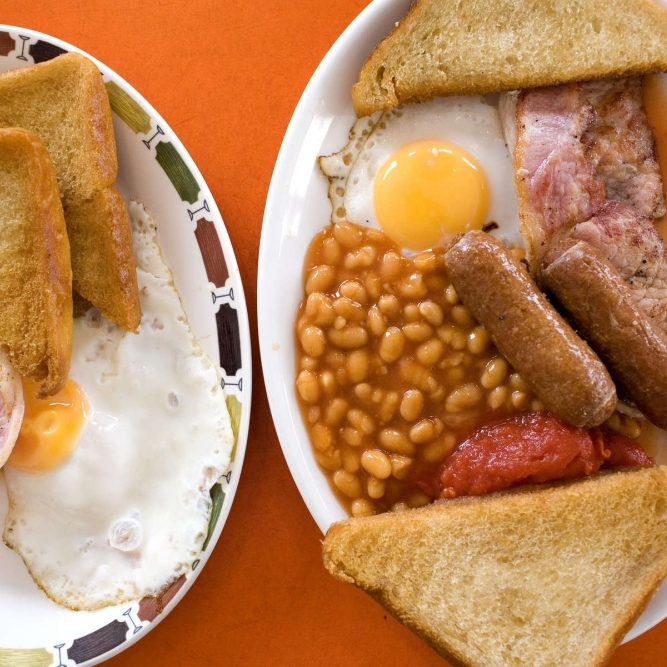 Zwei Teller mit Speck, Eiern, Toast, gebratenen Tomaten, Würstchen und Bohnen.