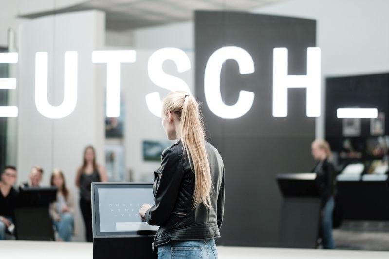 Eine junge Frau steht an einem Bedienungsterminal vor einer glänzenden LED-Wand