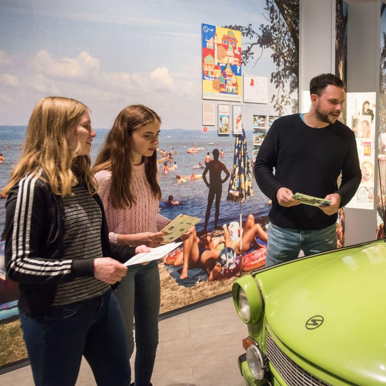 Zwei Mädchen im Teenager-Alter und ein Mann sehen sich einen Trabi mit einem Dachzelt an, im Hintergrund eine Foto-Tapete mit einem Seestrand