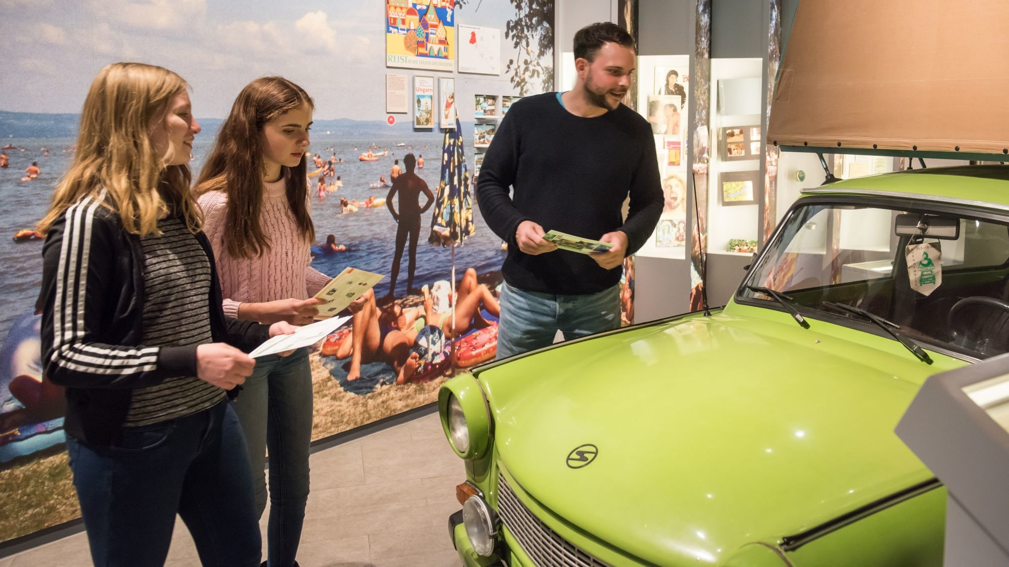 Two young girls and a young man are looking at the Trabi