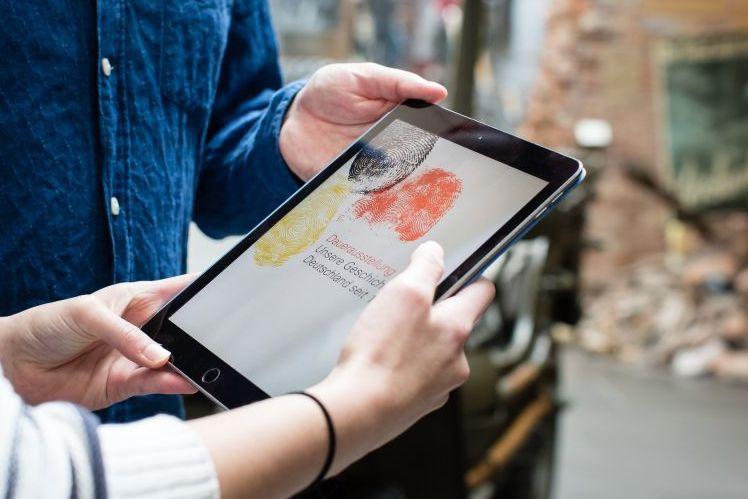 Im Zentrum des Bildes ein Tablet, auf dem ein hellgrauer Bildschirm mit drei Fingerabdrücke in schwarz-rot-gold und der Ausstellungstitel Unsere Geschichte. Deutschland seit 1945 zu sehen ist. Zwei Hände einer Frau und eine Hand eines Mannes halten das Tablet