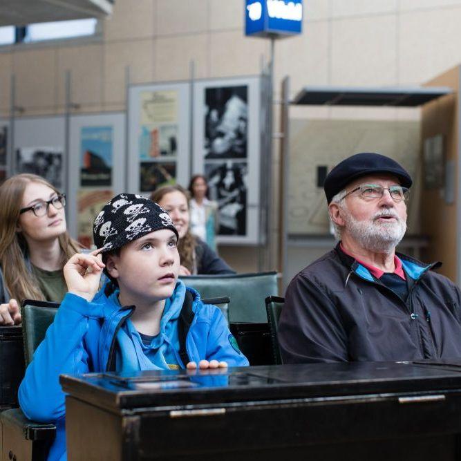Ein Junge mit Totenkopfmütze und ein älterer Herr mit Schirmmütze sitzen in einer Doppel-Stuhlreihe, hinter ihnen eine junge Frau