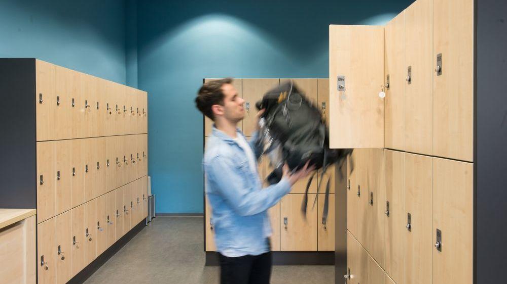 Ein Mann räumt seinen Rucksack in ein Schließfach